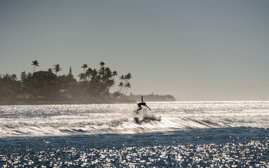 Ein Surfer auf einer Welle kurz vor der Einfahrt zum Hafen in Lahaina.